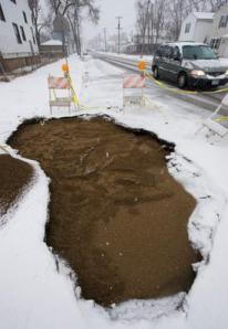 Drivers navigate around barriers surrounding an enormous hole left after work to repair a sewer problem at the intersection of Blaine and Garden streets.